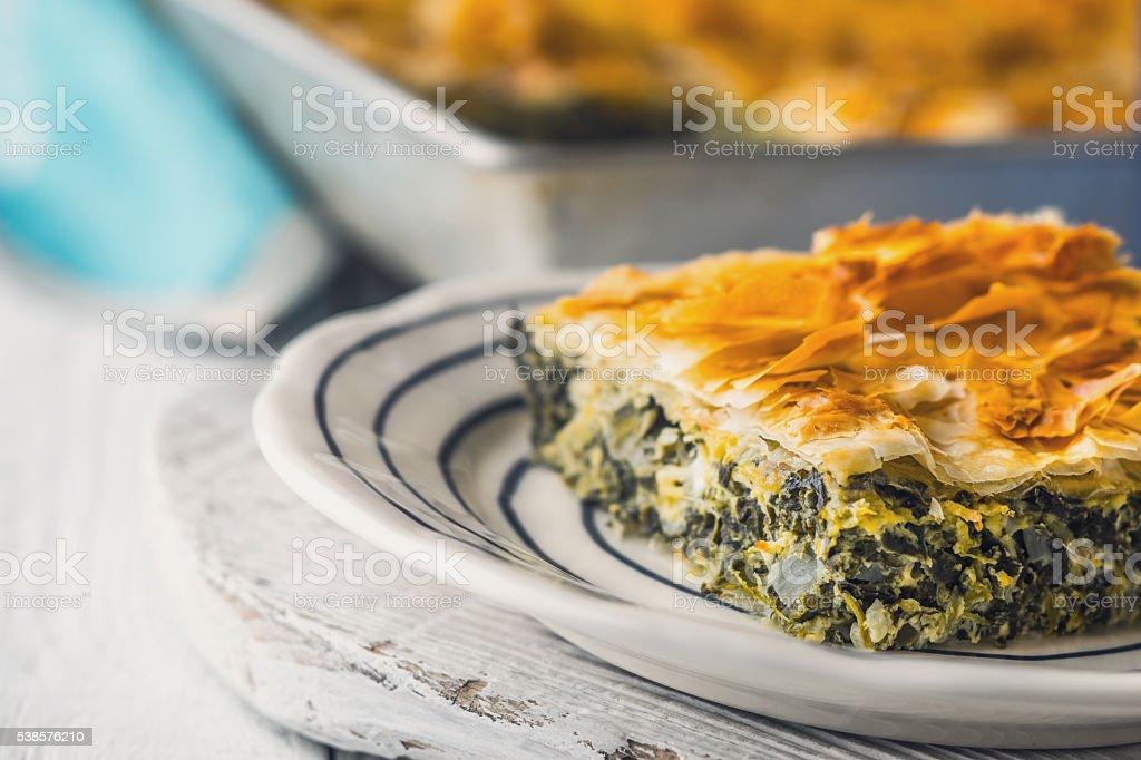 Greek pie spanakopita in ceramic plate on white  table  horizontal stock photo