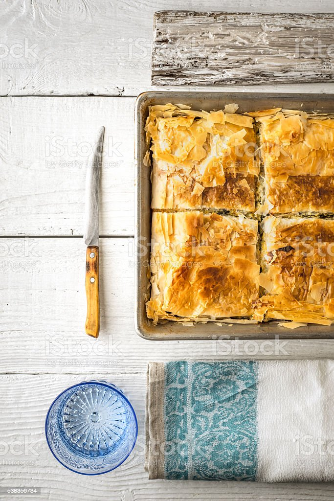 Greek pie spanakopita in metal pan  with table ware vertical stock photo
