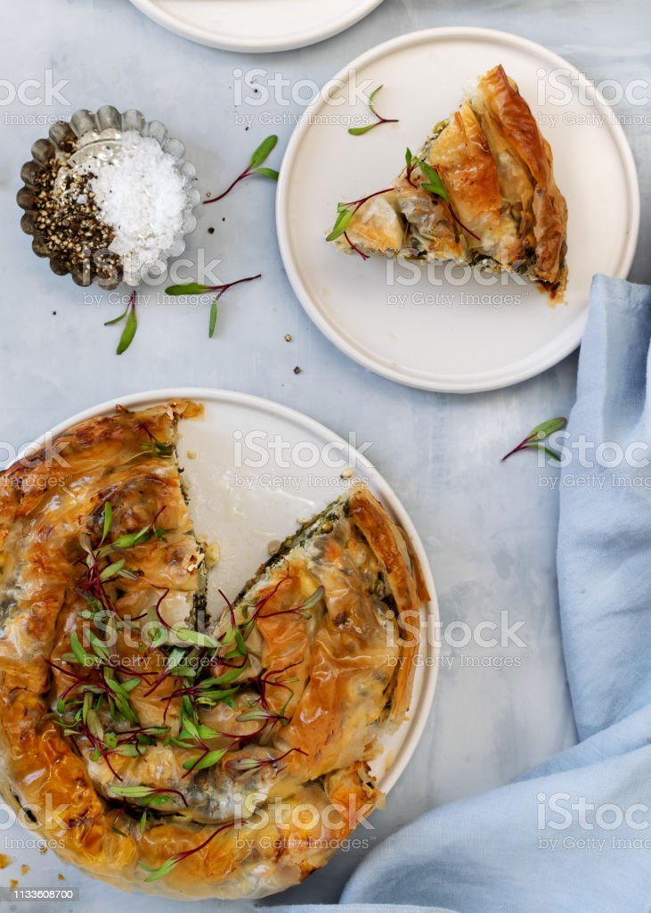 Greek Pie Spanakopita On Light Blue Background Ideas And Recipes For Vegetarian Or Vegan Spinach Pie From Fillo Pastry Cut In Slices Copy Space Top View Or Flat Lay Stock Photo
