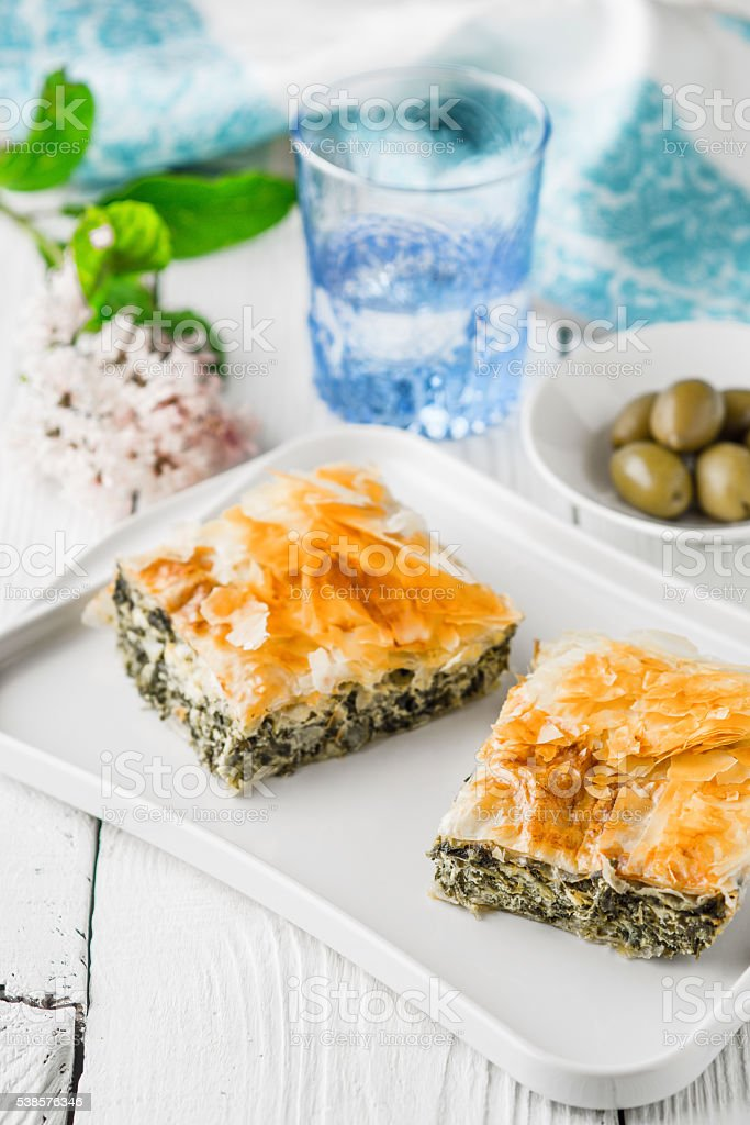 Greek pie spanakopita on the white plate with accessorizes vertical stock photo