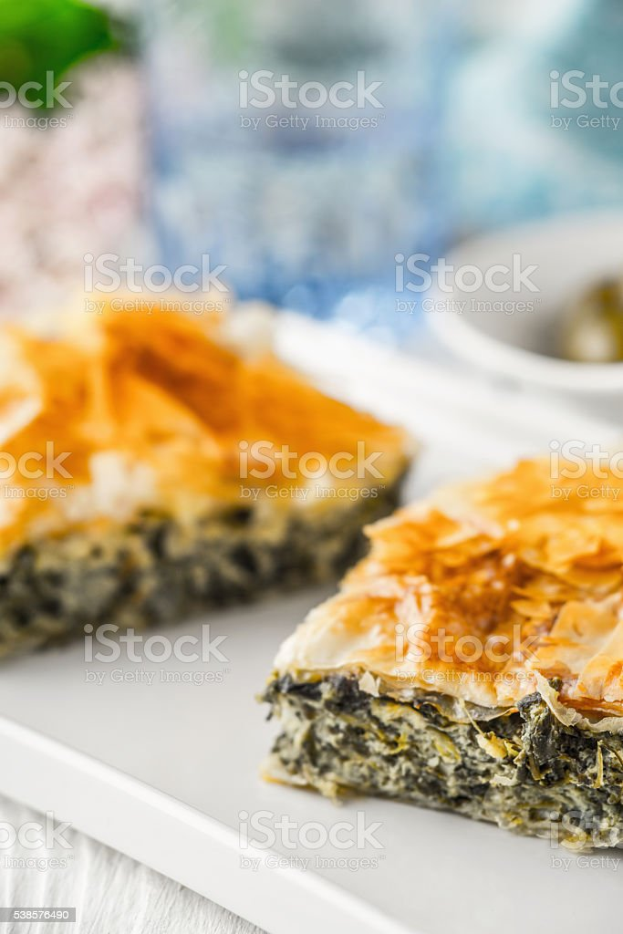 Greek pie spanakopita on  white plate with blurred accessorizes stock photo
