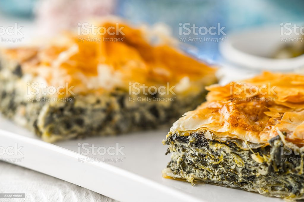 Greek pie spanakopita on white plate with blurred accessorizes horizontal stock photo