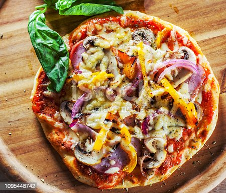 Greek pizza with mushrooms, ham, cheese, onions, pepper on wooden board