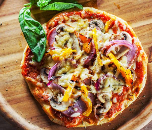 griechische pizza mit champignons, schinken, käse, zwiebeln, pfeffer auf holzbrett - fladenbrotpizza stock-fotos und bilder