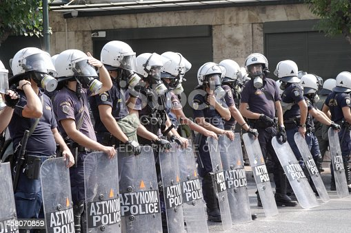 Athens, Greece - September 8, 2011:Greek Riot Police waiting for rioters near Syntagma Square in Athens, Greece in the daytime.  The police are all men and are in a row, to create a human shield. They have plexiglass shields, gas masks,and white helmets for their protection.  The word
