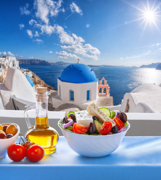 Greek salad against famous church in Oia village, Santorini island in Greece stock photo