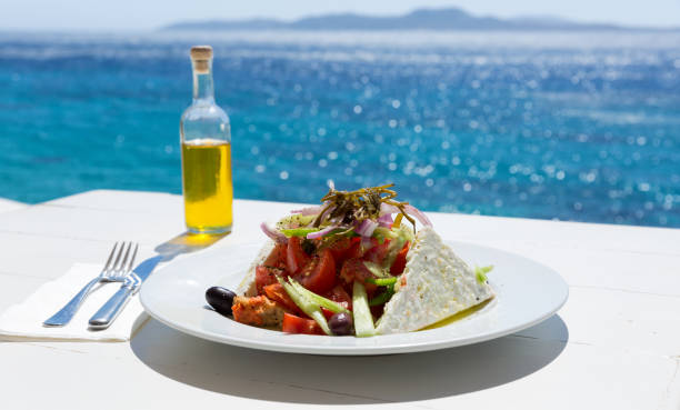 Greek salad and olive oil bottle Greek salad and olive oil on sunny sea setup mediterranean sea stock pictures, royalty-free photos & images