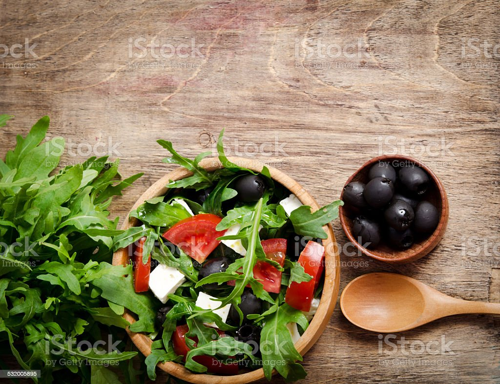 Greek salad in a wooden salad bowl on the table stock photo
