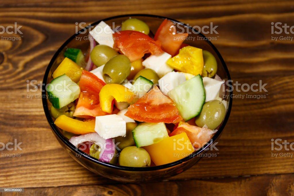 Greek salad in glass bowl on wooden table zbiór zdjęć royalty-free