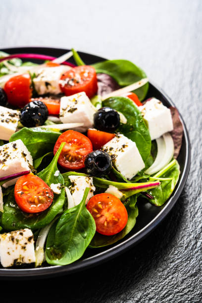 Greek salad on black stone background