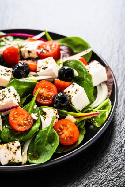 Griechischer Salat auf schwarzem Stein hintergrund – Foto