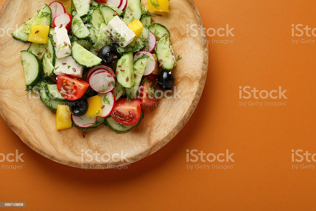 Greek salad on wooden plate stock photo