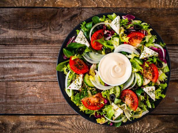 Greek salad on wooden table stock photo
