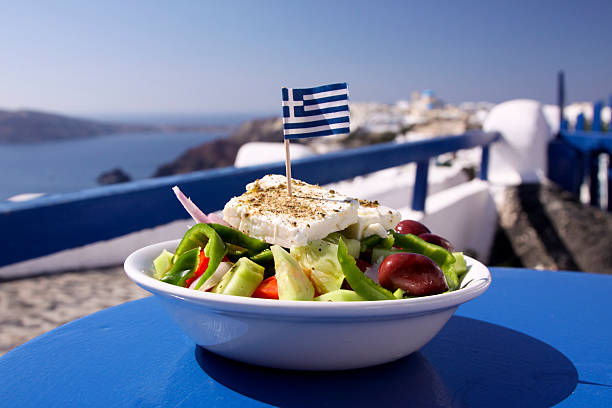 Greek salad served by the water in Santorini, Greece A perfect Greek salad, incorporating olives, green peppers and feta cheese, topped with a Greek flag, in Oia, Santorini feta cheese stock pictures, royalty-free photos & images