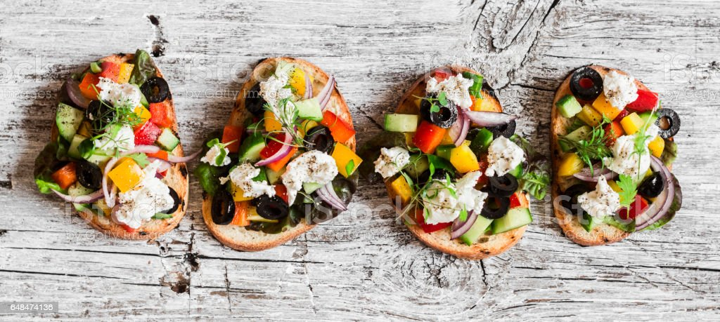 Greek salad style bruschetta on a wooden rustic board, top view. Delicious appetizers for wine or a snack стоковое фото