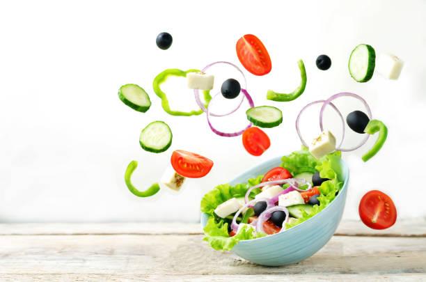 griechischer salat mit fliegenden zutaten zubereitung - gurke gesund stock-fotos und bilder