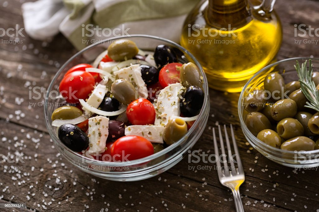 Greek salad with fresh vegetables, feta cheese and green olives wooden table royalty-free stock photo