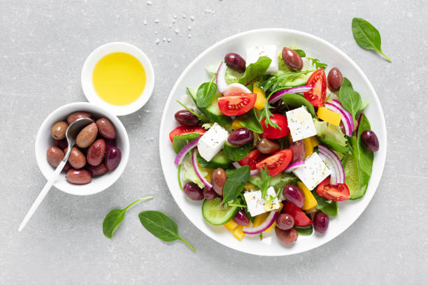 Greek salad with greens, olives and feta chesse on a white plate, top view stock photo