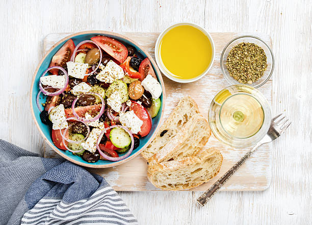 Greek salad with olive oil, bread, spices and white wine stock photo