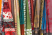 A display of colorful scarves for sale outside a vendor stall in the Plaka section of Athens.