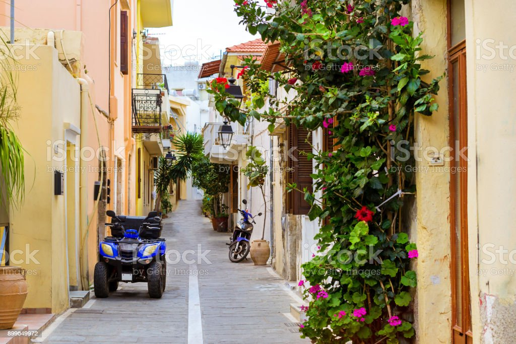 Narrow touristic street with parked Quad Bike and scooter. Walk...