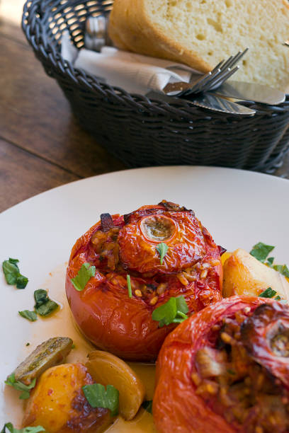 Greek Stuffed Tomatoes,  Gemista filled with rice, chopped vegetables and baked in a tomato sauce and basked of bread. Taken in Donoussa Island, Greece stock photo