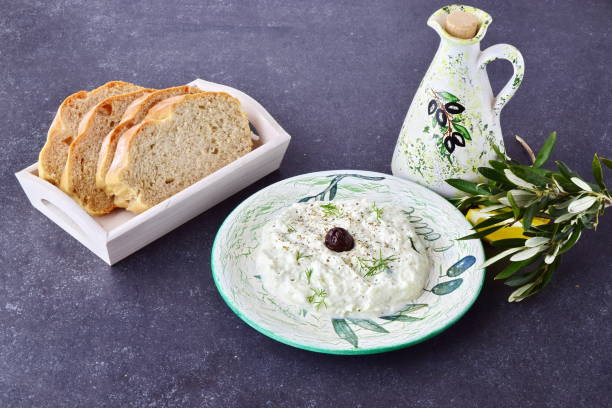 Greek traditional sauce tzatziki with olives, olive oil jar, lemon and bread on a grey abstract background. Healthy eating concept stock photo