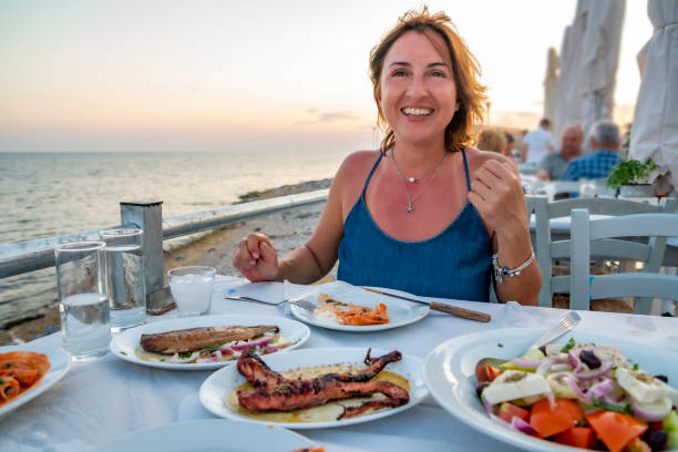 Greek woman enjoying from delicious greek food and ouzo. stock photo