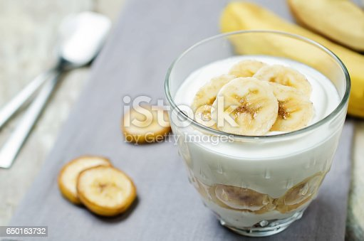 Greek yogurt banana parfait on a wood background. toning. selective focus