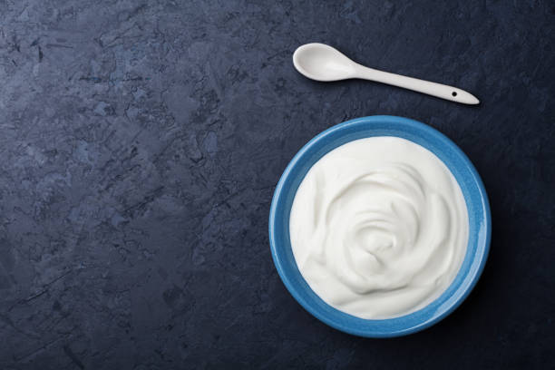 Greek yogurt in blue bowl on black table top view. Copy space for text. Greek yogurt in blue bowl on black table top view. Flat lay. Copy space for text. sour cream stock pictures, royalty-free photos & images