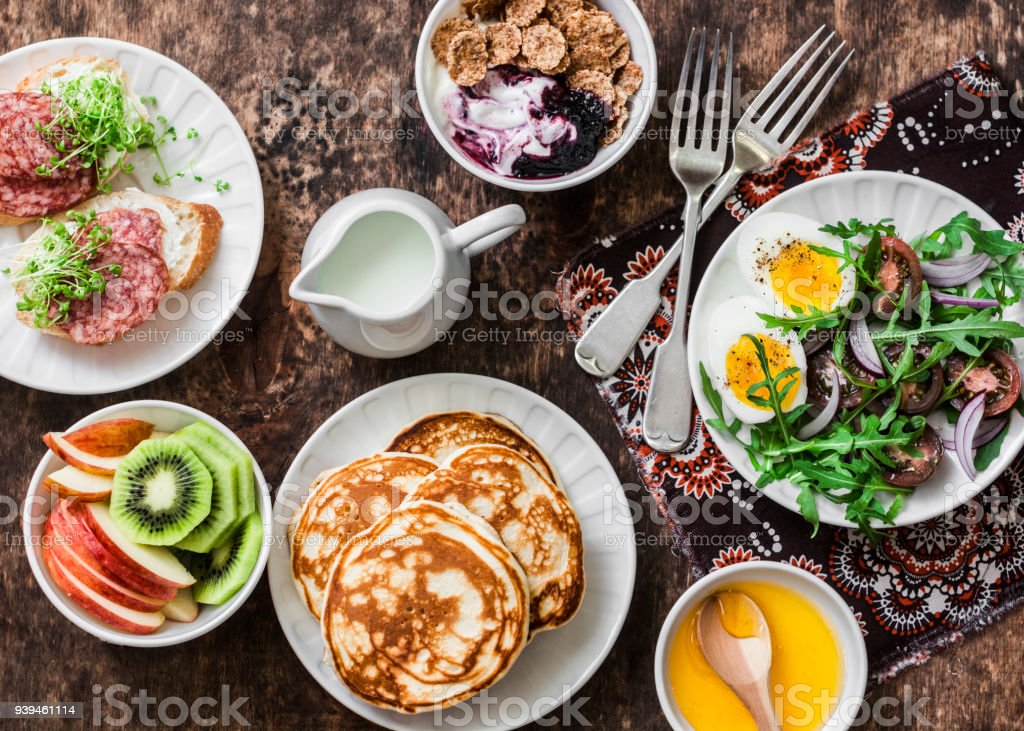 Greek yogurt with whole grain cereals and berry sauce, pancakes, arugula, cherry tomatoes, boiled eggs salad, kiwi, apples fruit, salami and cream cheese sandwiches on a wooden background, top view. Flat lay breakfast table stock photo