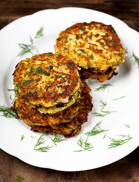 Greek Zucchini Fritters Kolokithokeftedes (Greek Zucchini Fritters with dill) on white platesee also: fritter stock pictures, royalty-free photos & images