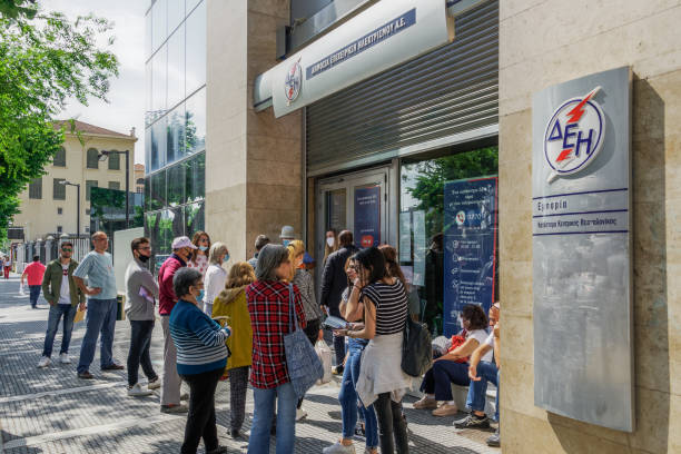 Greeks keep distance outside DEI-Public Power Corporation for electricity store, in line with decision to prevent COVID-19. stock photo