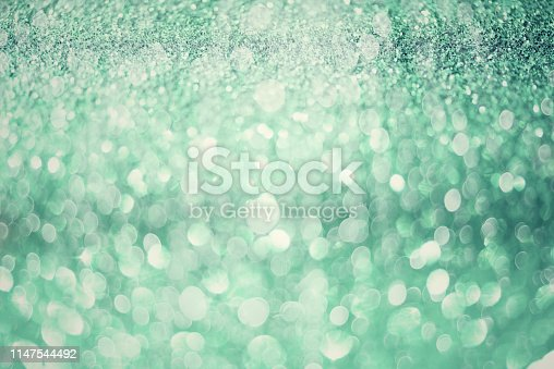 881350776 istock photo Green abstract bokeh lights. Shiny glitter background with copy space. New year and Christmas concept. Sparkling greeting card 1147544492