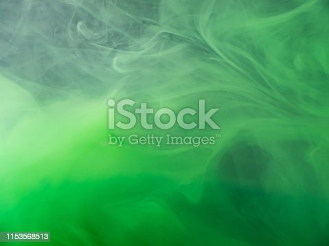 Green acrylic paint dissolving into water, abstract pattern. Close up view. Blurred background. Acrylic smoke under water, abstract background. Paint in liquid. Abstract art for wallpapers