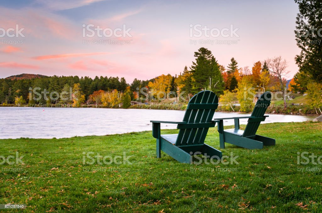 Green Adirondack Chairs on the Shore of a Lake stock photo