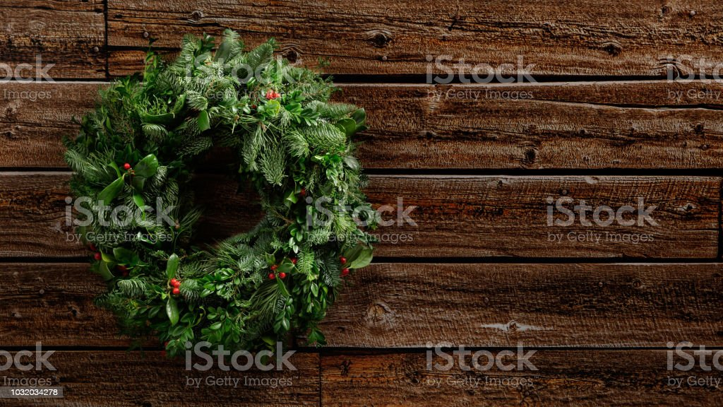 Grüne Adventskranz der Fir Misteln Zweige und Beeren an einer Vintage Holzwand hängen – Foto