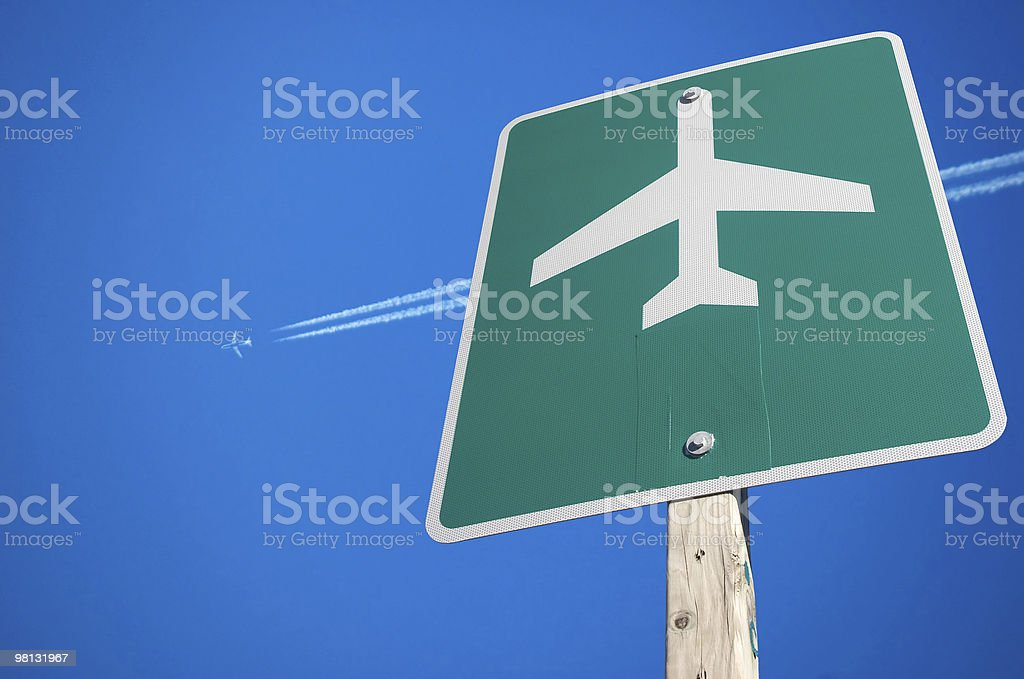 Green airport sign with flying jet in the sky background royalty-free stock photo