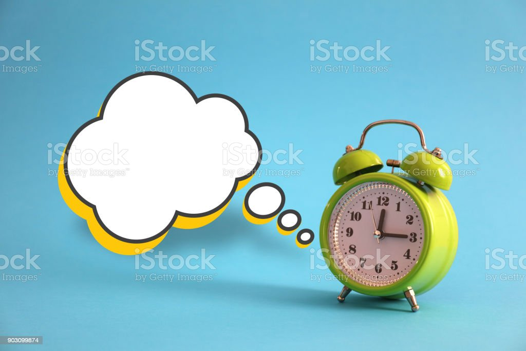 Green alarm clock on a blue background stock photo