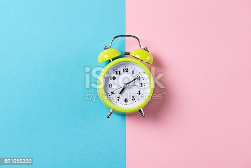 istock Green alarm clock with bells on blue and pink background, top view with copy space 821656332