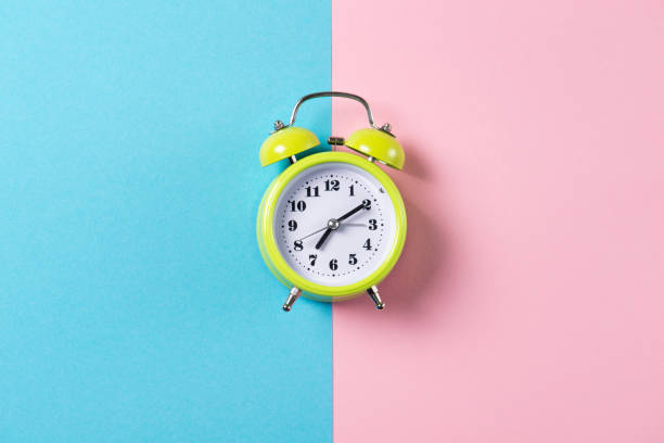 Green alarm clock with bells on blue and pink background, top view with copy space stock photo