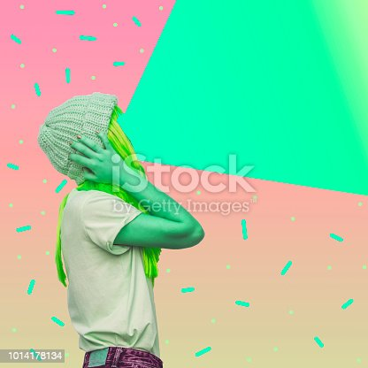 istock Green alien girl with a projector instead of a face emits light. 1014178134