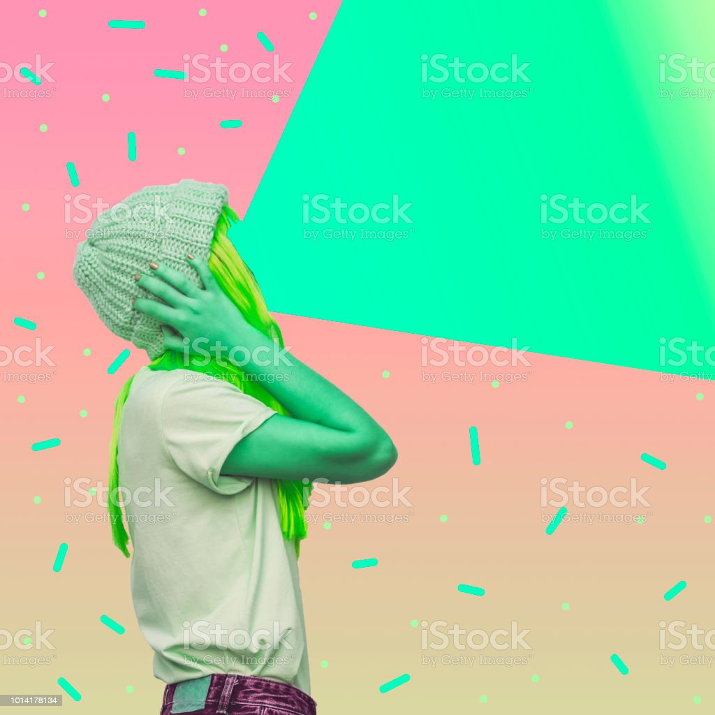 Green alien girl with a projector instead of a face emits light. stock photo
