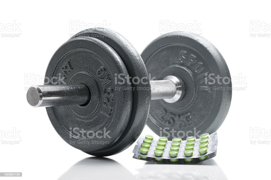 Green anabolic steroids next to a dumbbell stock photo