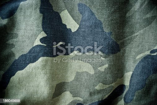 istock Green and black camouflage material background or texture 186045655