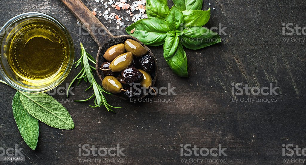Green and black Mediterranean olives in old cooking spoon stock photo