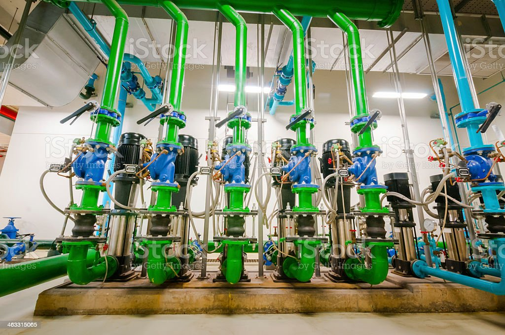 Green and blue industrial interior pipes and equipment stock photo