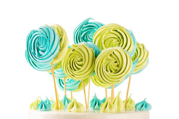 grünen und blauen lutscher baisers candy auf holzstab - lutscher cookies stock-fotos und bilder