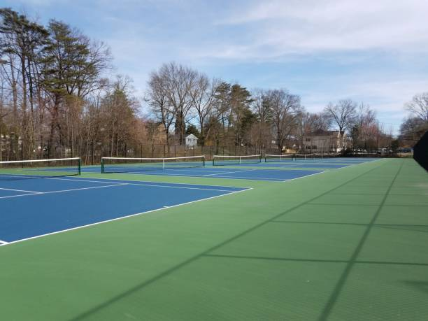 green and blue surface tennis courts with net stock photo