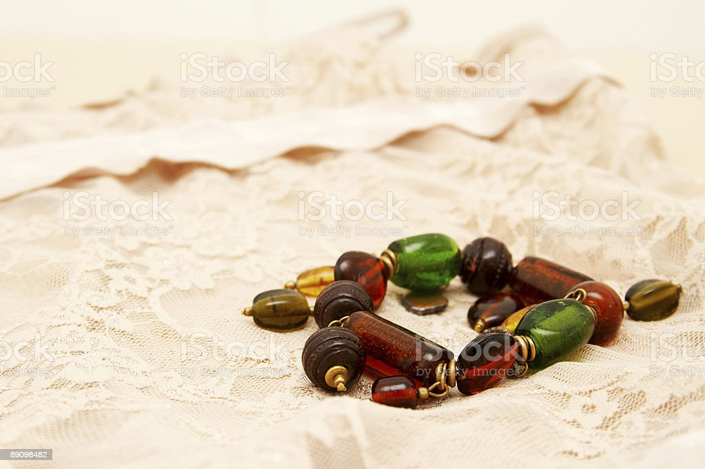 Green and brown bracelet lying on lingerie. royalty-free stock photo